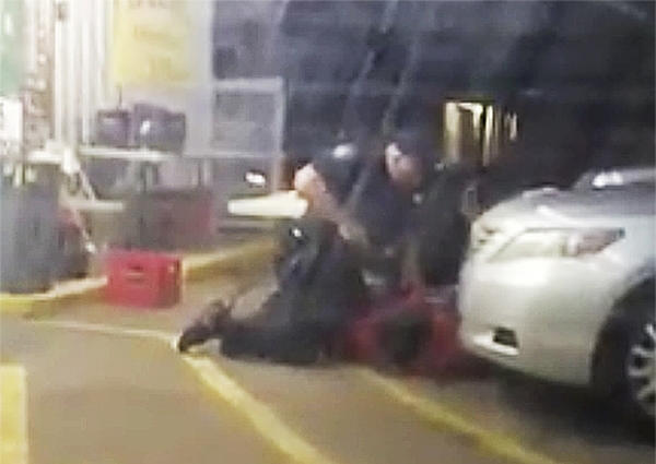 In this Tuesday, July 5, 2016 photo made from video, Alton Sterling is held by two Baton Rouge police officers, with one holding a hand gun, outside a convenience store in Baton Rouge, La. Moments later, one of the officers shot and killed Sterling, a black man who had been selling CDs outside the store, while he was on the ground. (Arthur Reed via AP)