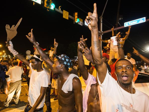 Protesters march Wednesday near the convenience store in Baton Rouge, La., where Alton Sterling was shot and killed.