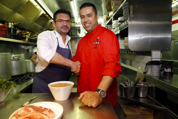 French chef Stephane Jégo (left) poses with Syrian refugee chef Mohammad El Khaldy before the Refugees Food Festival held in Paris in June.