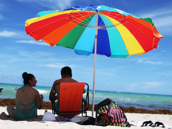 Tourists relax on Miami Beach last August. Travel experts had been predicting that this summer would bring out our desire to take vacations and have fun. The latest jobs report confirms it: Employers are hiring to help you enjoy the season.