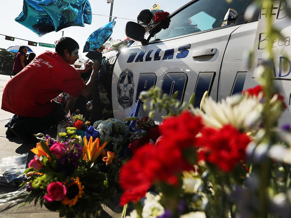 People write condolence notes to the fallen police officers at a growing memorial in front of the Dallas Police Headquarters, following the killing of five police officers.