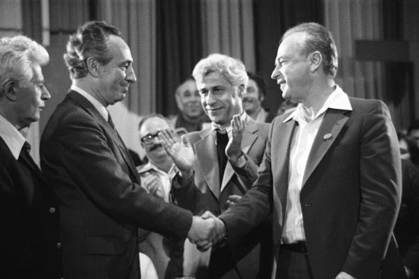 Peres (second from left), then the Israeli defense minister, congratulates Prime Minister Yitzhak Rabin on Feb. 23, 1977, in Tel Aviv, after learning that Rabin was elected by members of his party to represent the ruling Labor Party in the general elections.