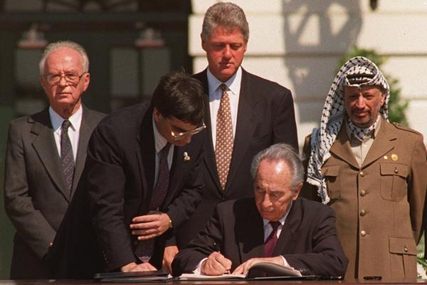Foreign Minister Peres signs the Mideast peace agreement on Sept. 13, 1993. Prime Minister Rabin (left), President Bill Clinton (center) and Palestine Liberation Organization Chairman Yasser Arafat look on from behind.