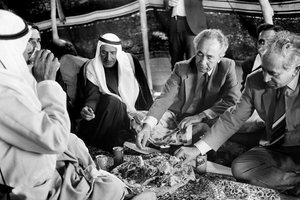 Peres enjoys a Bedouin-style meal under a traditional nomad's tent on Jan. 29, 1985. It was the prime minister's first visit to this minority, who number some 35,000 people and live in the Negev desert, south of Israel.