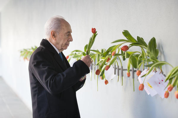 Then-President Peres places a tulip on the wall during his visit to the Dutch Theatre (Hollandsche Schouwburg) in Amsterdam on Sept. 29, 2013. The theater was used as a location to deport Jews during World War II and is now a monument.