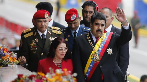 Venezuela's President Nicolas Maduro waves to supporters as he walks with his wife Cilia Flores in the capital Caracas on July 5, Venezuela's Independence Day. As the country's crisis has deepened, Maduro has lost support, but the military remains on his side.