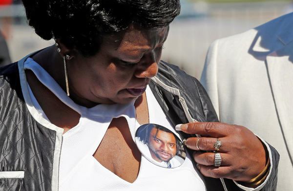 Valerie Castile, mother of Philando Castile, looks at a photo button of her son during a press conference on the state Capitol grounds in St. Paul, Minn., on Tuesday. Philando Castile was fatally shot by police July 6.