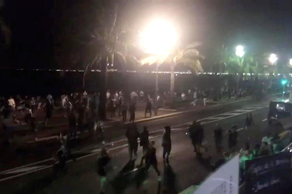 In this video screenshot, people run from the scene after a truck drove onto the sidewalk and plowed through a crowd that had gathered to watch fireworks Thursday in Nice.
