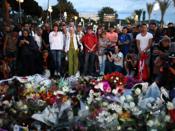 People gather and lay flowers on Nice's Promenade des Anglais on July 15. A French-Tunisian attacker left 84 people dead after driving a truck through crowds gathered to watch fireworks during Bastille Day celebrations. The attacker then opened fire on the crowd before being shot dead by police.
