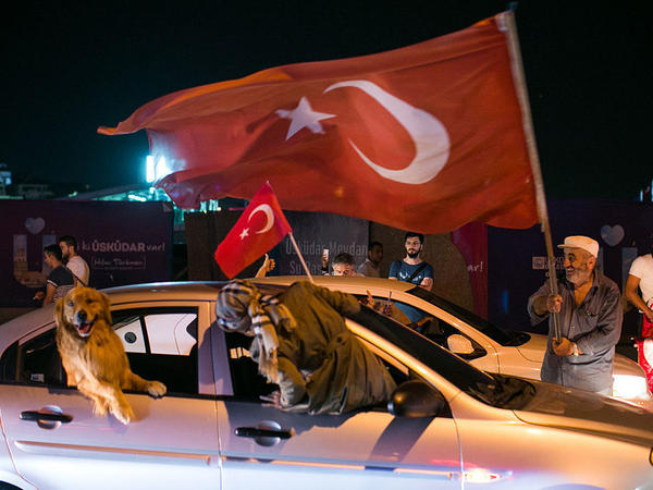 People drive next to a Turkish man waving a flag in Uskudar district in Istanbul on July 16 during a demonstration in support of Turkey's president.