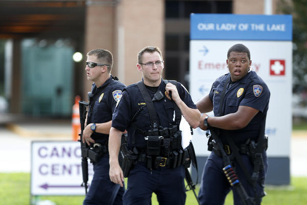 Police guard the emergency room entrance of Our Lady of the Lake Medical Center, where wounded officers were brought Sunday in Baton Rouge, La.