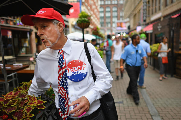 A man wears a large Trump button as people gather in downtown Cleveland for the first day of the Republican National Convention.