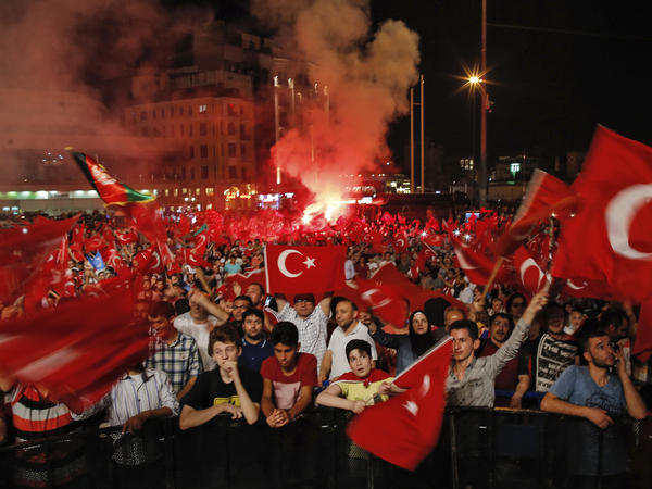 People wave Turkish flags Tuesday as they gather in Taksim Square in Istanbul, protesting against the attempted coup last Friday. The Turkish government accelerated its crackdown on alleged plotters of the failed coup against President Recep Tayyip Erdogan.