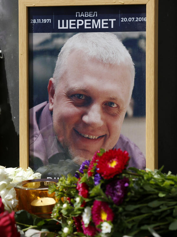 A portrait of journalist Pavel Sheremet is surrounded with flowers and candles near where the car he was driving exploded, killing him on Wednesday.