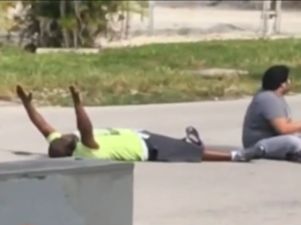 In a video filmed on Monday, Charles Kinsey (left) lies next to the autistic patient he was trying to help, holding his hands up in an effort to assure the North Miami police that they aren't a threat. Kinsey was later shot in the leg by the police.