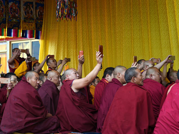 In a photo provided by China's Xinhua News Agency, Tibetan monks take smartphone pictures during the Kalachakra ritual in Tibet.