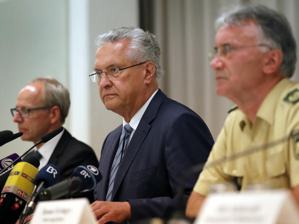 Bavarian Interior Minister Joachim Herrmann (center), briefs the media in Ansbach, Germany on Monday. Bavaria's top security official says a man who blew himself up after being turned away from an open-air music festival in Ansbach was a 27-year-old Syrian who had been denied asylum.