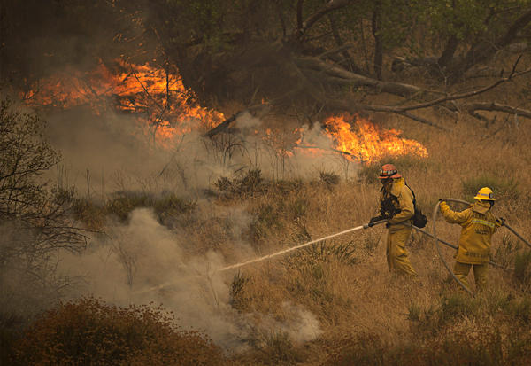 Firefighters battle part of the Sand Fire after flames jumped across a road in Santa Clarita, Calif., on Sunday. As the blaze changed direction multiple times over the weekend firefighters were forced to retreat and thousands of people have been evacuated from their homes.