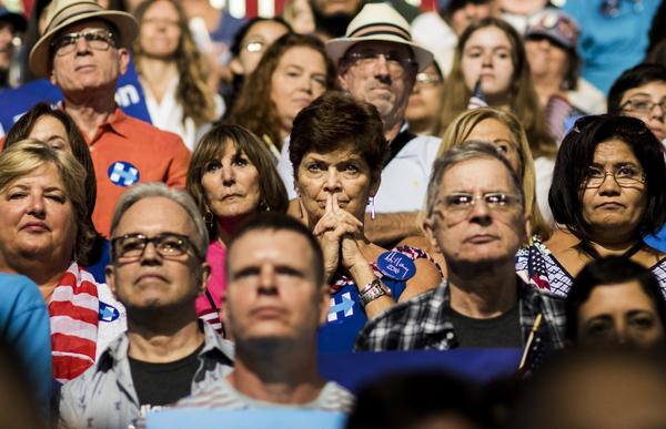 Audience members watch as Democratic presidential nominee Hillary Clinton and her running mate, Sen. Tim Kaine, speak at a rally in Miami.