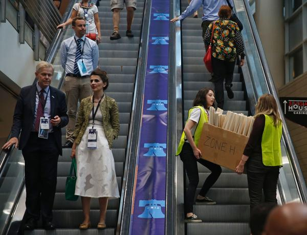 Convention staff carry a box of signs to the upper levels of the Wells Fargo Center to hand out to the crowd.
