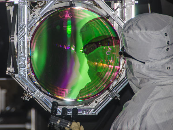 Lasers and mirrors are used to carefully measure shifts in space-time. To avoid contamination, protective clothing must be worn at all times.