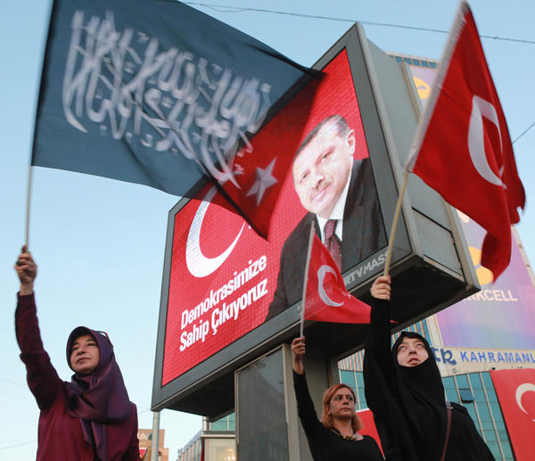 Women wave flags in front of a billboard bearing a picture of President Recep Tayyip Erdogan on Aug. 2 in Ankara's Kizilay Square during a protest against the failed military coup in July.
