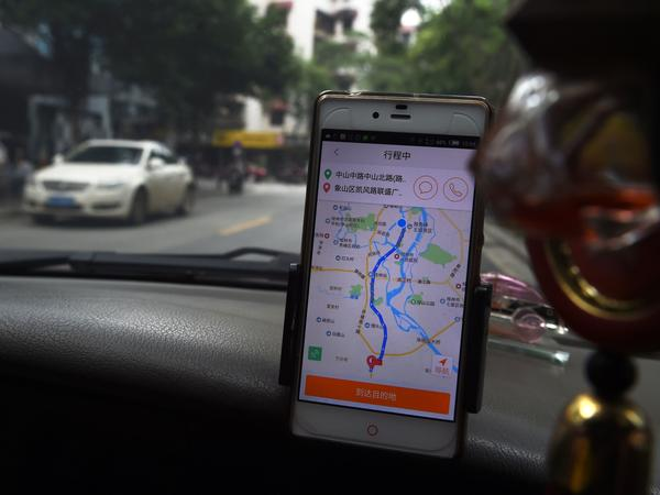 A taxi driver uses the Didi Chuxing app in Guilin, in China's southern Guangxi region, on May 13. The company is joining up with Uber's Chinese unit, its former rival.