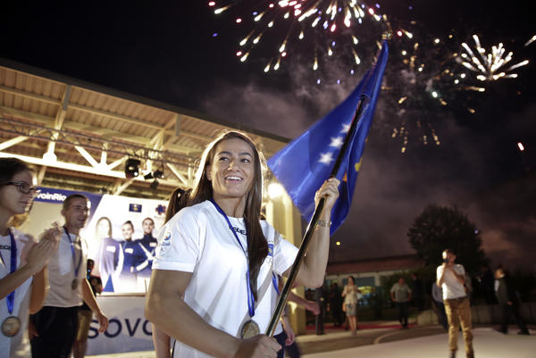 Kosovo's Malinda Kelmendi, who competes in judo, waves the country's flag in the capital city Pristina on July 29. Kosovo, which declared independence in 2008, is sending eight athletes to its first Olympic Games.
