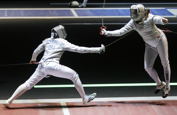 Ibtihaj Muhammad (left) competes with Tunisia's Hela Besbes during a women's team sabre qualifying match at the 2011 World Fencing Championships in Catania, Italy.
