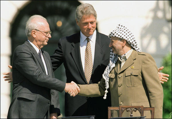 Israeli Prime Minister Yitzhak Rabin (left) and Palestine Liberation Organization Chairman Yasser Arafat (right) shake hands at the White House in front of President Bill Clinton in September 1993. The new play <em>OSLO</em> is a dramatization of events that led to a historic agreement.