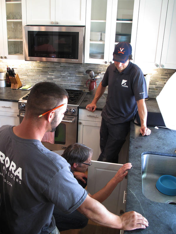 Nathaniel May (under sink) and his crew with Aurora Custom Builders goes through the final check list on a kitchen renovation outside Boston.