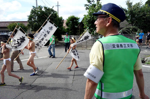 Locals volunteer as crossing guards for the parade through town in Nagano Prefecture. The boys walk about a mile in sweltering July heat.