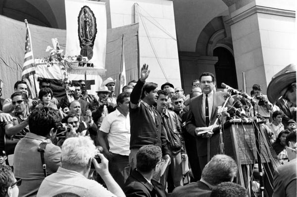 Chavez, leader of the Delano grape pickers' strike, waves to the crowd from the steps of the California Capitol in Sacramento, on April 11, 1966. Chavez led his strikers and followers on a more than 300-mile, 25-day pilgrimage from Delano to Sacramento in an attempt to meet with Gov. Pat Brown on Easter Sunday.