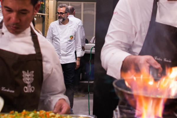 Chef Massimo Bottura checks with cooks as they prepare a gourmet soup kitchen dinner at RefettoRio Gastromotiva restaurant in Rio de Janeiro.