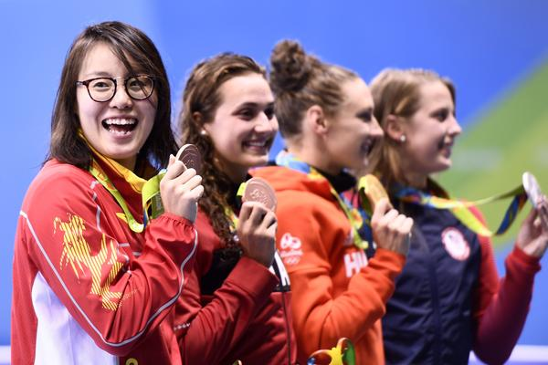 China's Fu Yuanhui (left) celebrates her bronze medal win in the women's 100-meter backstroke with Canada's Kylie Masse, Hungary's Katinka Hosszu and the U.S.'s Kathleen Baker.