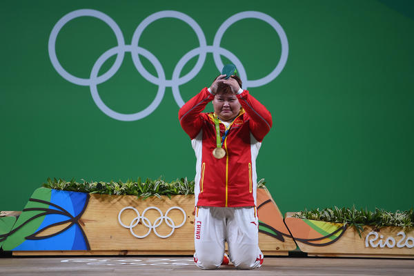 Gold medalist Meng Suping of China kneels on the podium during the medal ceremony for the women's weightlifting 75 kg group on Aug. 14 in Rio de Janeiro.