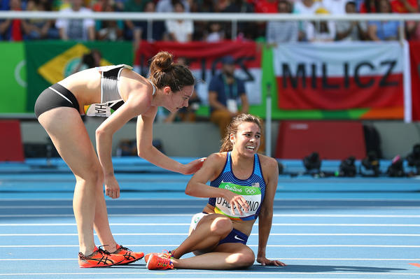 Nikki Hamblin of New Zealand (left) assists Abbey D'Agostino of the United States after a collision during a women's 5,000-meter heat on Tuesday. A moment earlier, D'Agostino had helped Hamblin when they both fell.