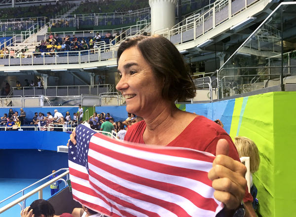 Leslie Fischer holds up an American flag as she cheers for her daughters, Makenzie and Aria.