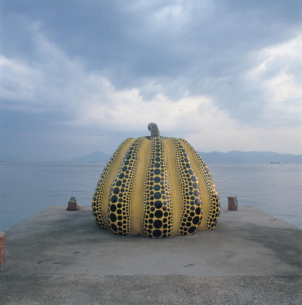 Yayoi Kusama's work <em>Pumpkin  </em>perches at the end of an old concrete pier.<em></em>