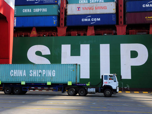 A truck carries a container past a ship at the port in Qingdao, in China's Shandong province on Feb. 15, 2016. China's sagging economy has hurt the shipping industry this year.
