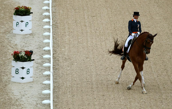 Adelinde Cornelissen of Netherlands and her horse, Parzival, compete in the Dressage Individual Grand Prix event at the Olympic Equestrian Center on Wednesday. Cornelissen dropped out of the competition because her horse was ill.