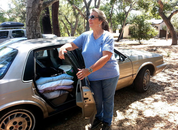 Marge Giaimo stands with her gold Oldsmobile, where she currently sleeps.