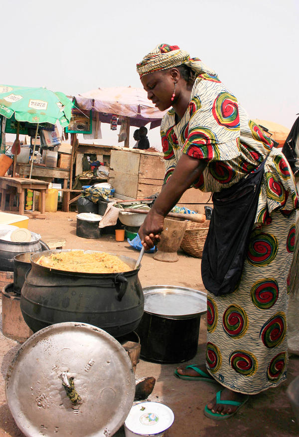 "A food vendor in Kano, Nigeria, prepares jollof rice outdoors in an iron pot. When it comes to jollof, my Nigerian friend Ronke Onadeko argues, ""the taste of perfection is smoke-flavoured."""