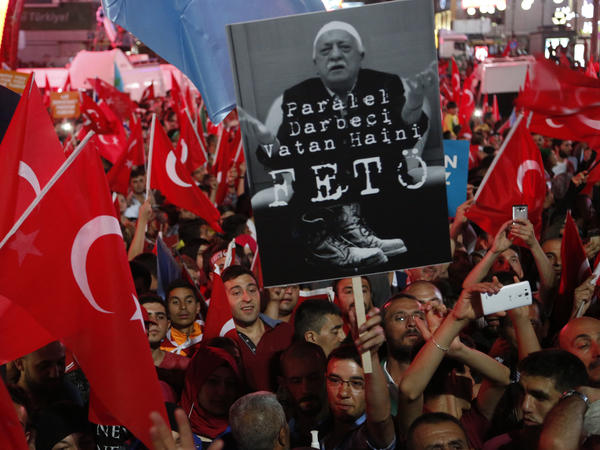 """Pro-government supporters in Ankara wave Turkish flags and hold signs showing Fethullah Gulen on July 20. The sign says """"The coup nation traitor, FETO."""" FETO stands for """"Fethullah Terrorist Organization."""""""