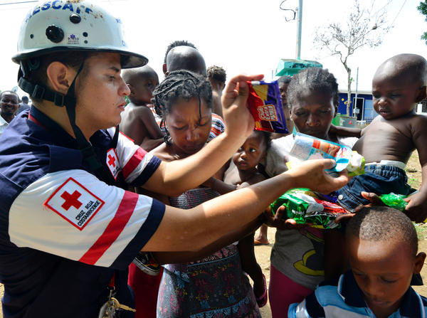 A Costa Rican Red Cross member distributes food to migrants in an encampment of Africans in Penas Blancas, Guanacaste, Costa Rica, on July 19. In a makeshift camp hundreds of tents shelter Haitians, Congolese, Senegalese and Ghanaian migrants waiting to continue their journey to the United States.