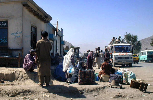 "Afghans wait roadside with their belongings leaving Kabul, Afghanistan, on Sept. 20, 2001. Taliban leaders, warning of a possible U.S. attack, urged Afghans to prepare for a long ""holy war"" against the United States. The Taliban were driven from power two months later, but remain a deadly insurgent force to this day."