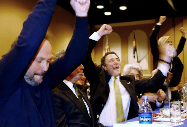 Billy Crystal (from left), New York City Mayor Michael Bloomberg, and Dan Doctoroff, New York City deputy mayor of economic development, cheer after the United States Olympic Committee announced in November 2002 that New York City would represent the U.S. in a bid to host the 2012 Summer Olympics.