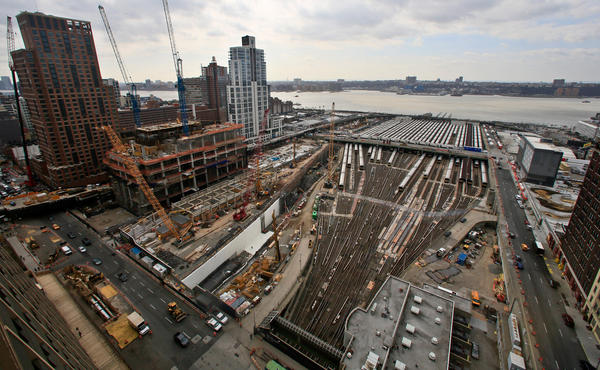The Hudson Yards project site in 2014 shows ongoing construction of skyscrapers alongside parked Long Island Rail Road trains. A $20 billion undertaking, Hudson Yards will fill 28 acres between the Hudson River and 10th Avenue with 14 skyscrapers after completely covering the train yards with a platform foundation.