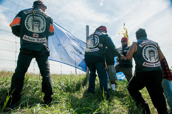 Members of Native Descendents, an all-Indian motorcycle club from Southern California, hang the La Jolla tribal flag at a construction site for the Dakota Access pipeline.
