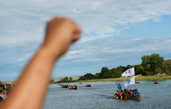 People raise their fists in solidarity as canoes arrive at a protest camp that sprang up to demonstrate against the pipeline. The canoe flotilla had representatives of tribes from across the Pacific Northwest, who had navigated the Missouri River from Bismarck to Cannon Ball to show their support.